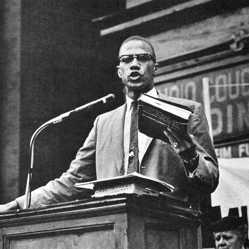 Malcolm X Holding Book Doing Speech